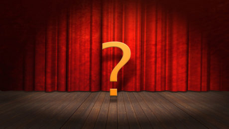 A questionmark in front of a theatre curtain
